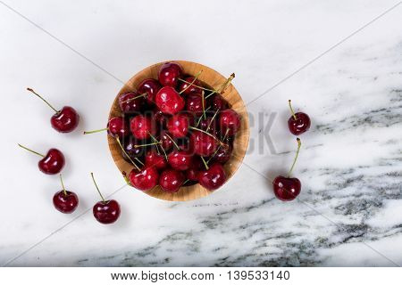Overhead view of a bowl of red cherries on natural marble counter.