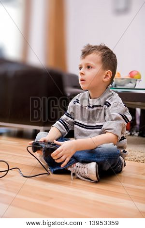 Young boy in living room with video game controller .