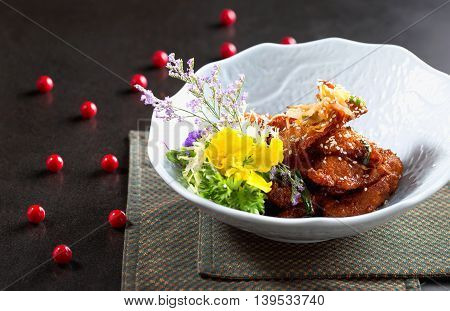 Deep fried pork on white bowl with herbs on the table