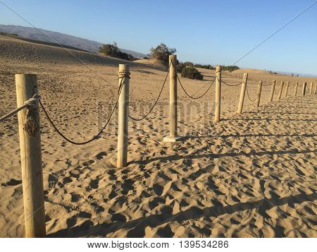 A shot of a fence between dunes in the sand of a beach