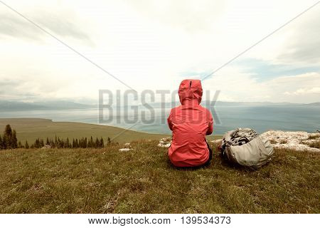 successful woman backpacke hiking on mountain peak cliff