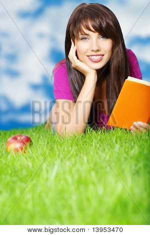 young woman reading book in the grass. sky background