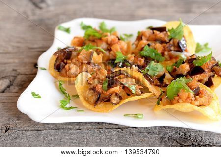Chopped roasted eggplant with tomatoes and green parsley on potato chips. Delicious snack on a plate and on old wooden table. Tasty fried eggplant recipe. Closeup