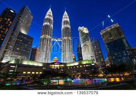 KUALA LUMPUR MALAYSIA - July 18 2016: Petronas Twin Towers with Musical fountain at night in Kuala Lumpur Malaysia