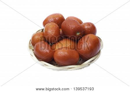 Red tomatoes with drops of water in a basket on a white background