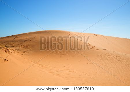 Big red dune on the background of blue sky. Phan Thiet, Vietnam