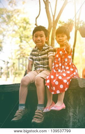 Happy asian siblings smiling and looking at camera on nature background. Children relaxing outdoors in the day time with sunlight travel on vacation. Sister hand on her brother shoulder. Warm tone.