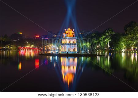 HANOI, VIETNAM - JANUARY 10, 2016: Night on Hoan Kiem lake. View on the Tower Turtles and red bridge. Historical landmark of the city Hanoi, Vietnam