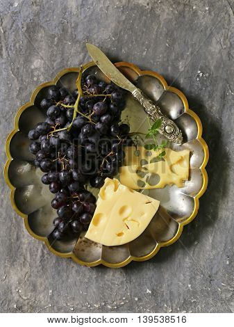cheese and fresh black grapes on vintage silver plates