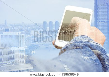 Double exposure image of smart phone with cityscape background,Communication technology concept
