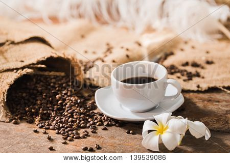 Coffee Cup And Coffee Beans On Wood Table