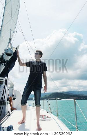 Young handsome man on the white yacht in the open sea the ocean