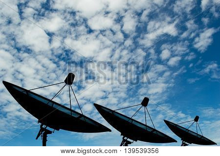 Three satellite dishes transmission data on background blue sky