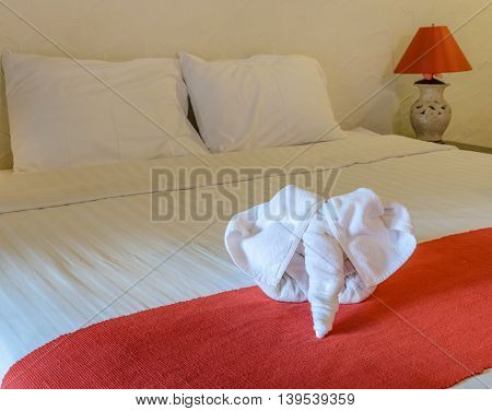 White towel in elephant shape on white bed in Thai style hotel bedroom