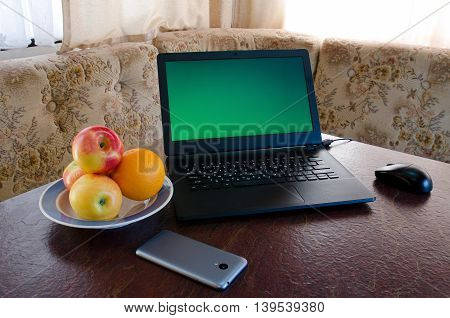 Open laptop on a table in a cozy kitchen with a plate of fruit smartphone