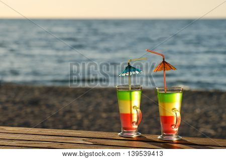 Two cocktails with straws on a wooden table top in the sun on the beach empty space