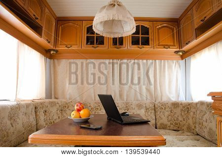 Open notebook with a fruit platter and a smartphone on a table in a small cozy kitchen