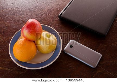 Dish of fruit a smartphone a laptop on the table top view