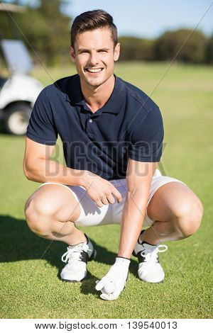 Portrait of man placing golf ball on tee while crouching at field