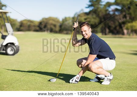Side view of man placing golf ball on tee while crouching on field