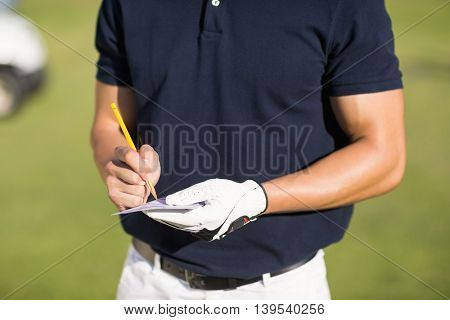 Midsection of golfer writing on score card while standing at golf course
