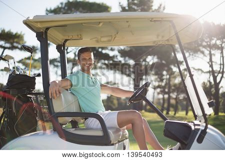 Portrait of smart man sitting in golf buggy on field