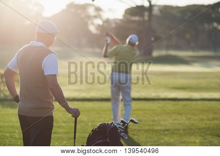 Golfer men standing on field during sunny day