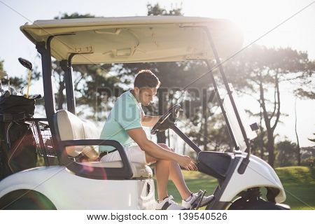 Side view of golfer man sitting in golf buggy on field