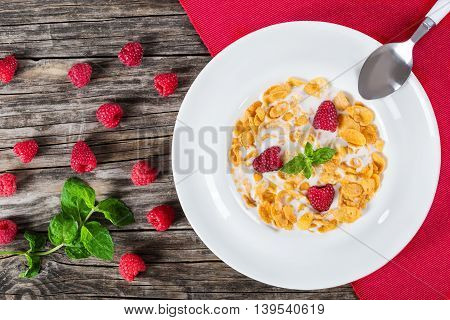 crispy corn flakes with raspberry and cold milk decorated with mint leaves in white wide rim plate on table mat with spoon on wooden worktop traditional and quick breakfast view from above