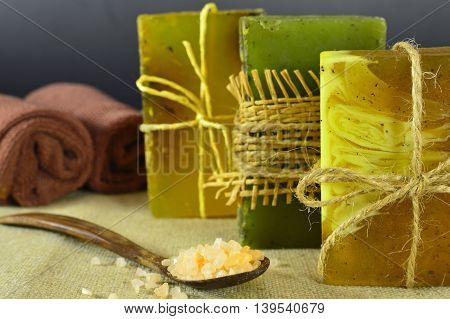 Three soap bars with spoon of scented salt and towels