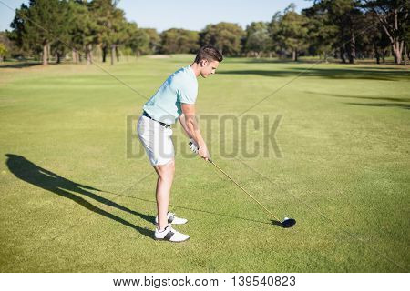 Full length side view of young man playing golf while standing on field
