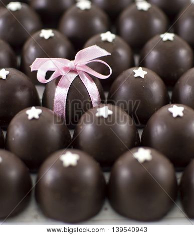 Close up of decorated chocolate candies and one chosen candy with pink bow
