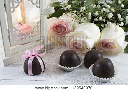 Romantic still life with chocolate candies, white roses and burning candle in lantern