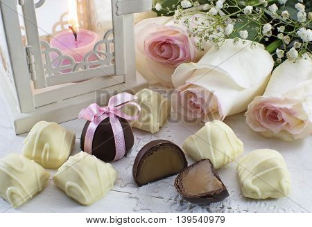 Romantic still life with black and white chocolate candies, white roses and lantern