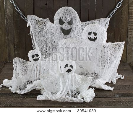 Ghosts family on wooden background, Halloween still life