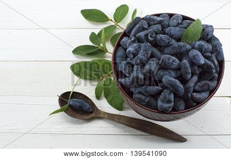 Blue honeysuckle berries in wooden bowl with spoon on white