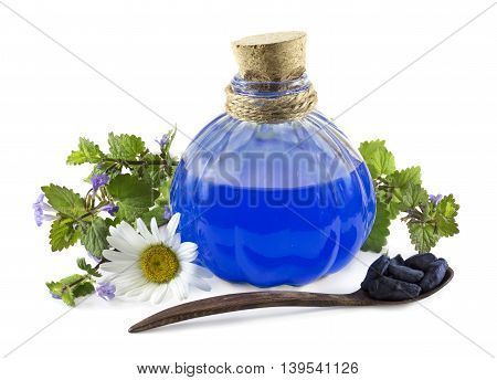 Glass bottle with blue healing remedy, chamomile and spoon with honeysuckle berries isolated on white