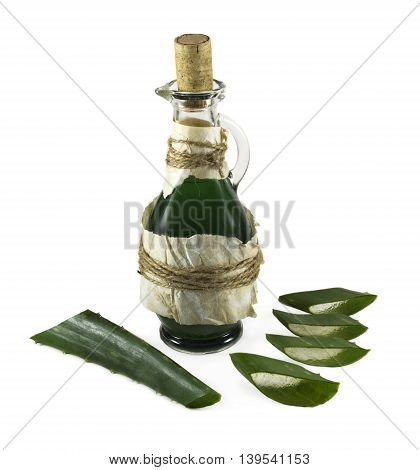 Ancient glass bottle with green remedy and aloe vera pieces isolated on white