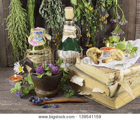 Homeopathic still life with healing herbs, book, glassware and candles