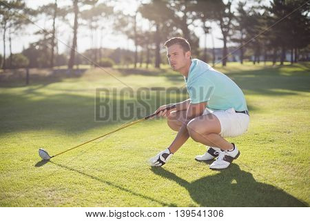 Full length of golfer man placing golf ball on tee while crouching at field