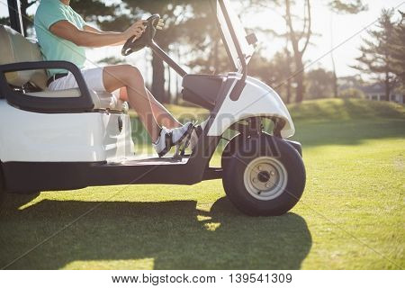Low section of golfer man driving golf buggy on field