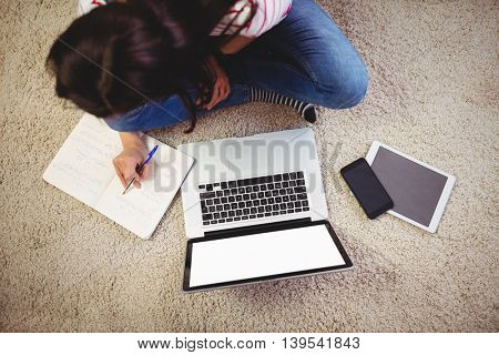 High angle view of woman sitting with laptop on rug at home