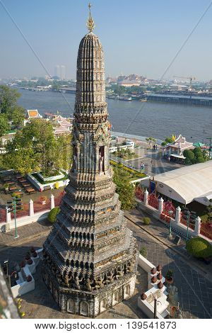 One of the towers of the temple Wat Arun in the background of the urban landscape. Bangkok, Thailand