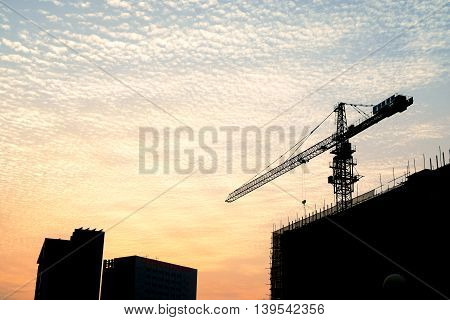 Silhouette Of Sunset Scene With Tower Crane On The Construction Site Building In City