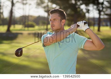 Handsome golfer man taking shot while standing on field