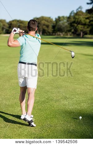 Rear view of golfer man taking shot while standing on field