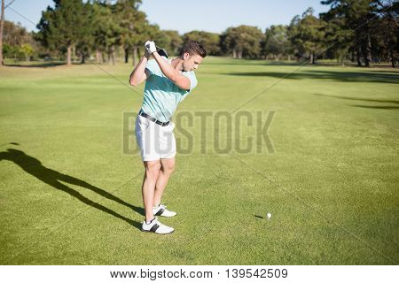 Full length of young golfer taking shot while standing on field
