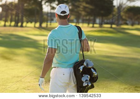 Rear view of golf player carrying bag while standing on field