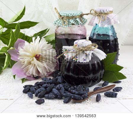 Three jam jars with honeysuckle berries and peony flower