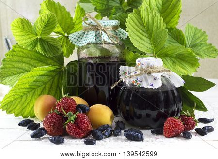 Summer still life with jam jars, berries and fruits on green leaves background